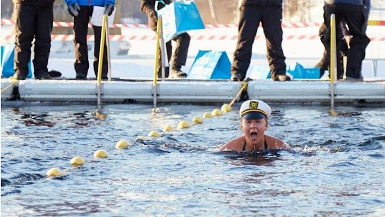 Sanna Näsström simmar i en iskall älv med en kaptensmössa på huvudet.