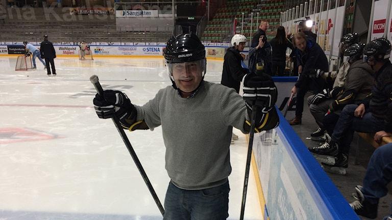En man i ishockeyhjälm står på skridskor vid sargkanten och ler.