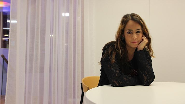 Yamile Lindgren sitter vid ett bord på sitt kontor.