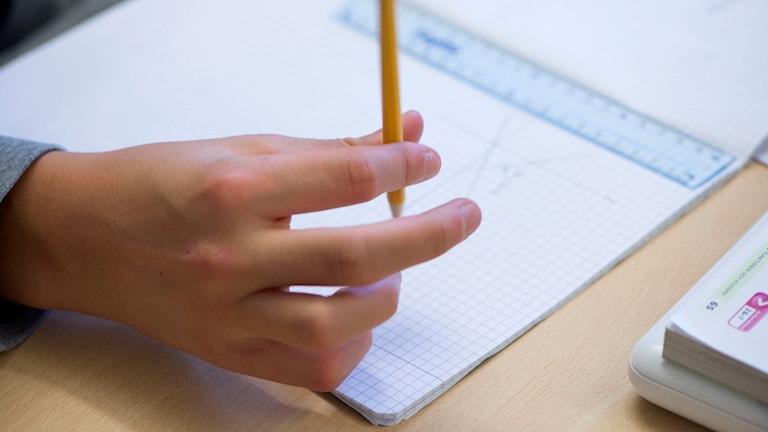En hand håller i en penna.