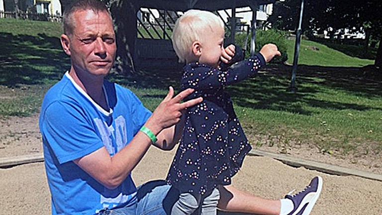 En bild på en man som sitter med sin dotter i sandlådan. Mannen heter Paul Nilsson och är hyresgäst i Marieberg.