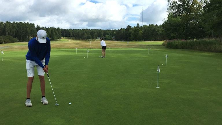 Emanuell Olofsson befinner sig på en golfbana och puttar sin golfboll mot hålet.