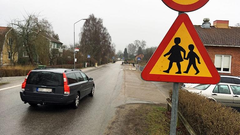 """Varningsmärket """"Varning för barn"""" och väg med bil."""