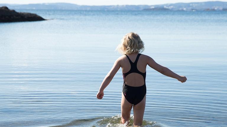 En liten flicka går ut i vattnet.