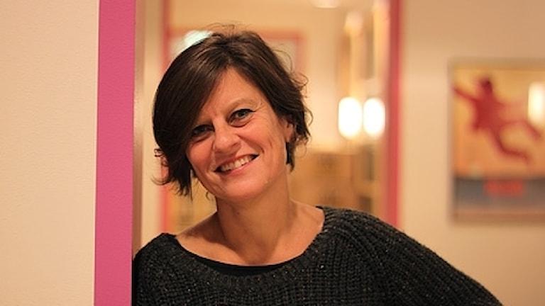Lena Martinsson står lutad mot en dörrkarm.