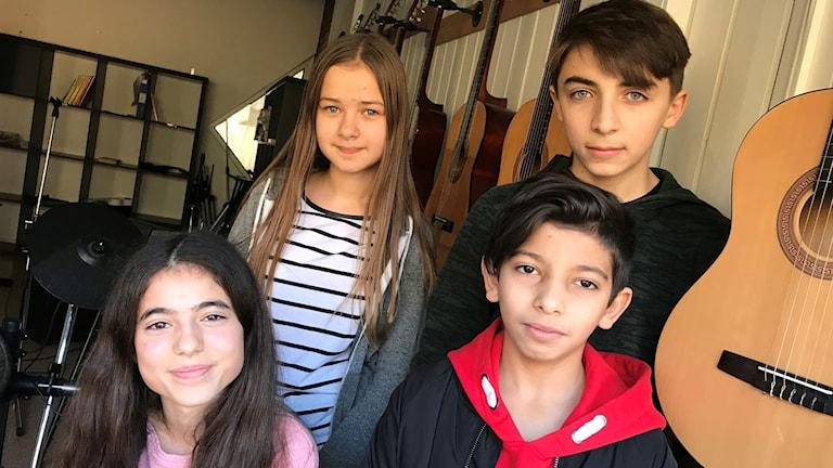Fyra ungdomar står i ett rum med musikinstrument.