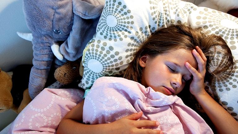 Ett sjukt barn ligger nedbäddat i sängen.