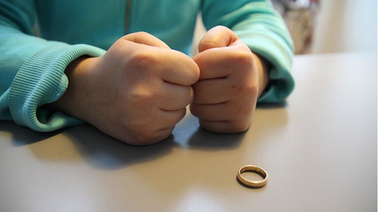 Barn med knutna nävar tittar på en guldring som ligger på bordet.