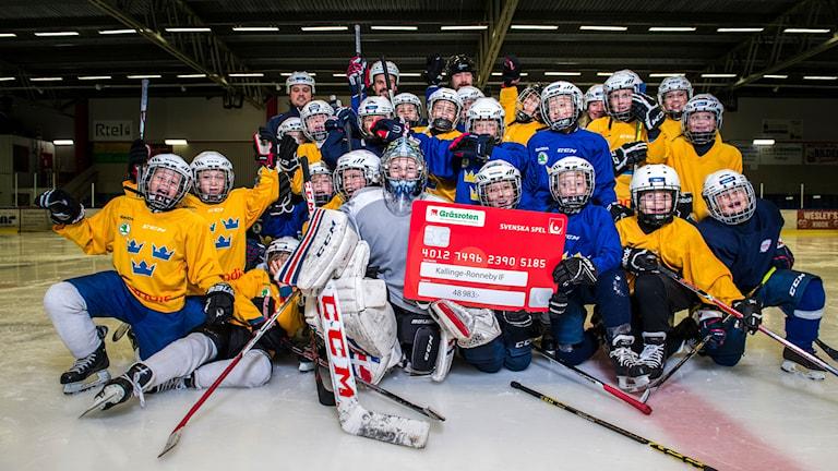 Kallinge-Ronneby IF:s ungdomalag håller upp en check från Svenska Spel.