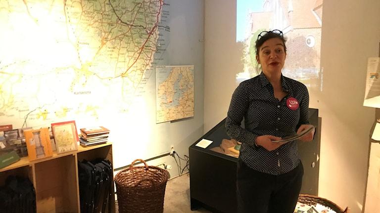 Kvinna står framför en karta över södra Sverige, bland allehanda Blekingerelaterade saker.