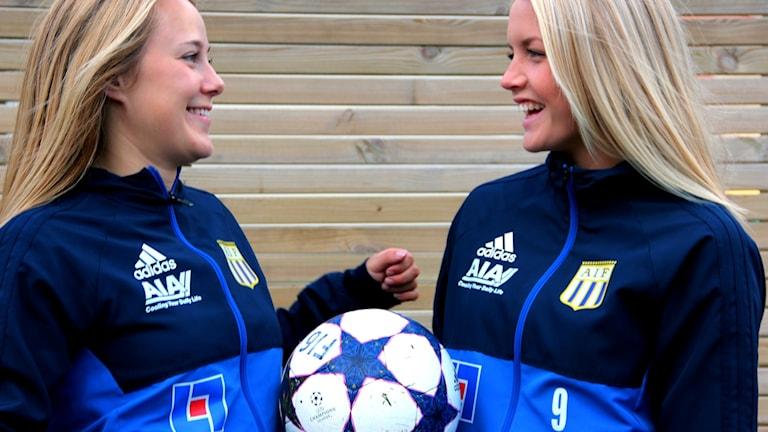 Maja Ericsson och Ellinor Månsson från Asarums IF står med en fotboll mellan sig.