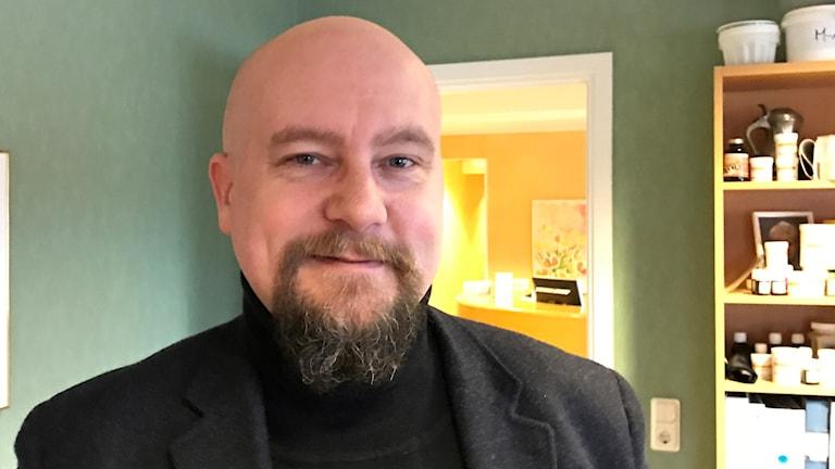 Närbild på en man med skägg och rakat huvud.