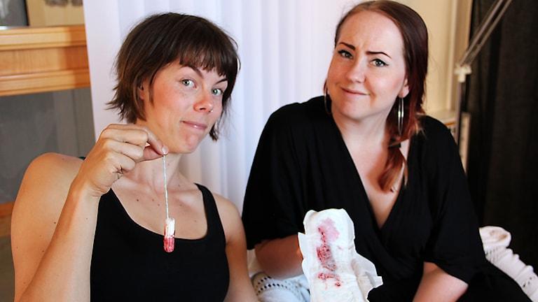 En bild där stina håller upp en blodig tampong och Matilda en blodig binda.