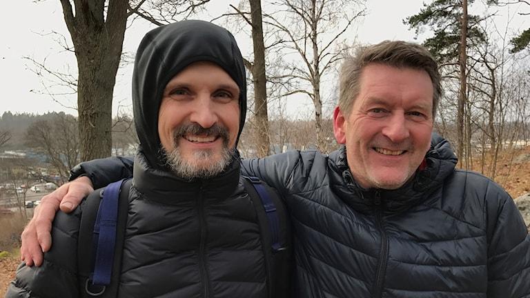 Två män står tätt bredvid varandra.