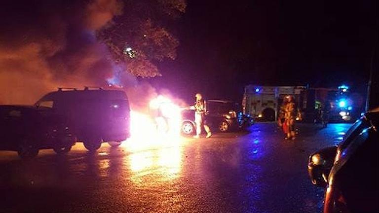 En bil som brinner medan räddningstjänst släcker.