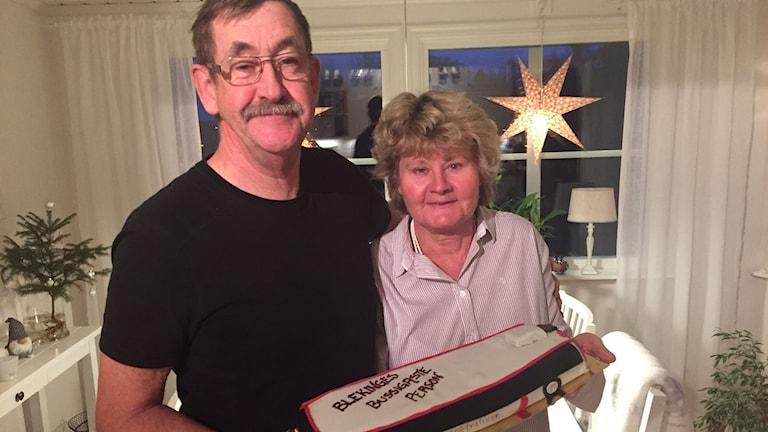 Grannarna Mats Johansson och Lena Johansson håller i tårtan tillsammans.