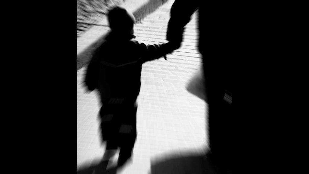 Siluetten av ett barn som håller en vuxen i handen.