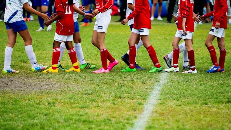 Nederkropparna på två fotbollslag iklädda fotbollsskor som tackar för matchen.