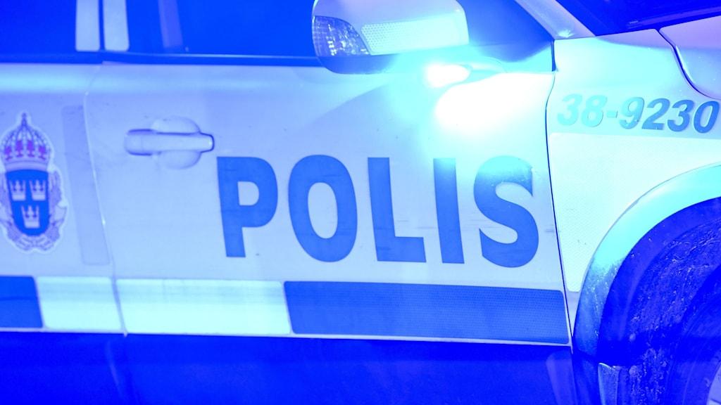 Polisbil med blå-ljusen tända.