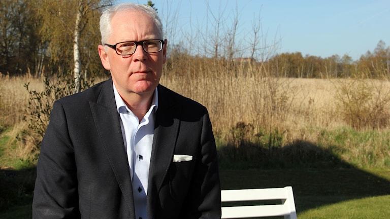 En porträttbild på advokaten Christer Holmqvist utomhus.