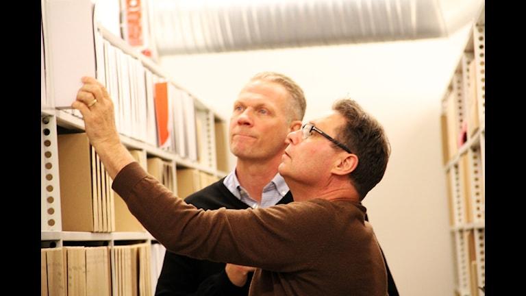 Jim Olsson och Bo Lundqvist står i polisens arkiv och letar.