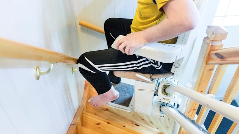 Man i rullstol som förs upp för trappa
