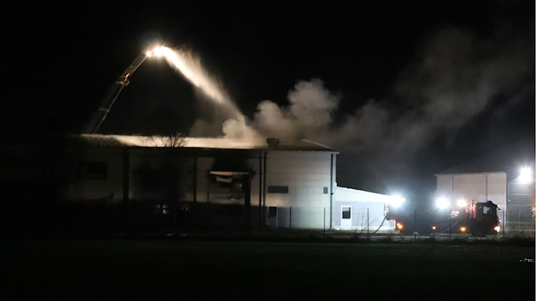 Industrihall i mörk natt. En stor kran sprutar ned vatten över taket. Rökmoln lyfter mot mörk himmel.