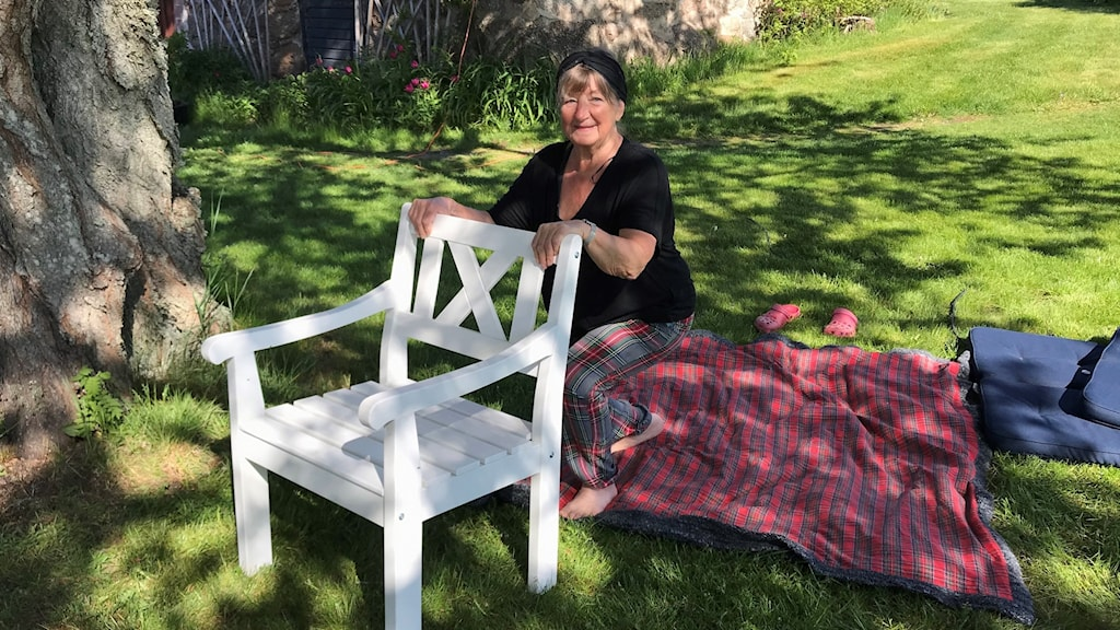 Barbro Ågren gympar med hjälp av en stol utomhus