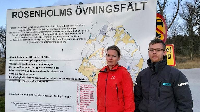 En kvinna och en man framför skylt med information om Rosenholms Övningsfält.