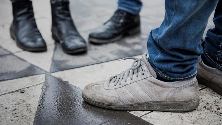 Fötter iklädda skor på ungdomar som står och pratar.