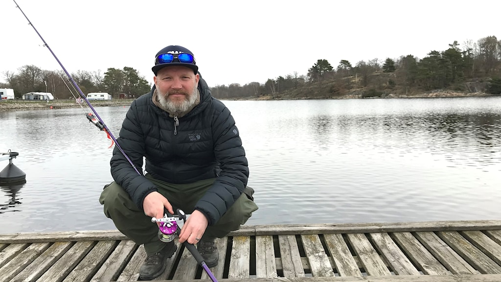 Man sitter på huk framför skärgården, med ett fiskespö i handen.