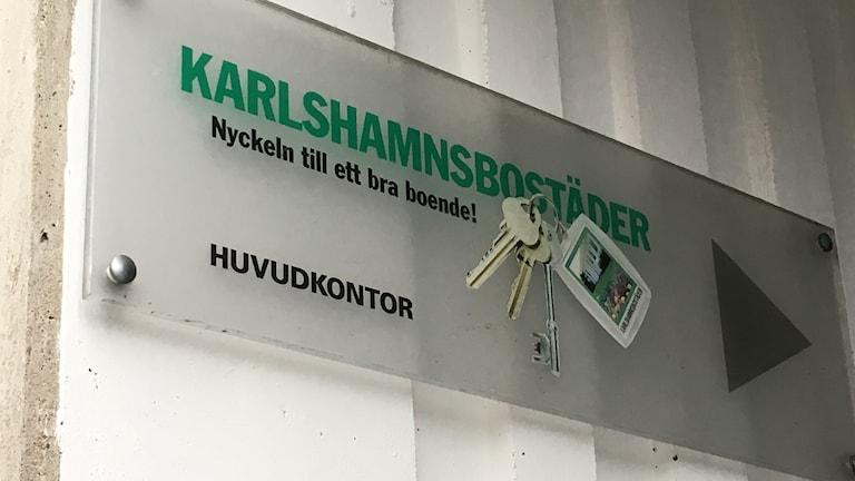 Närbild på en skylt där det står Karlshamnsbostäder på.