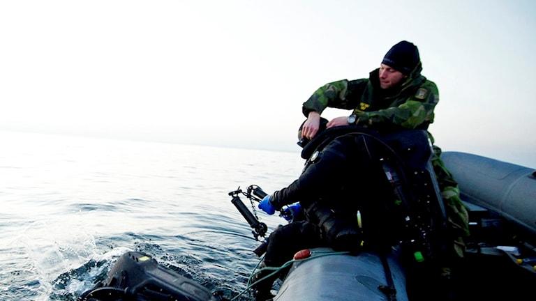 Dykare på gummijolle, får hjälp med utrustningen.