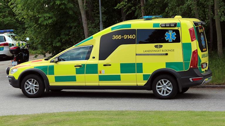 En gul ambulans sedd från sidan.