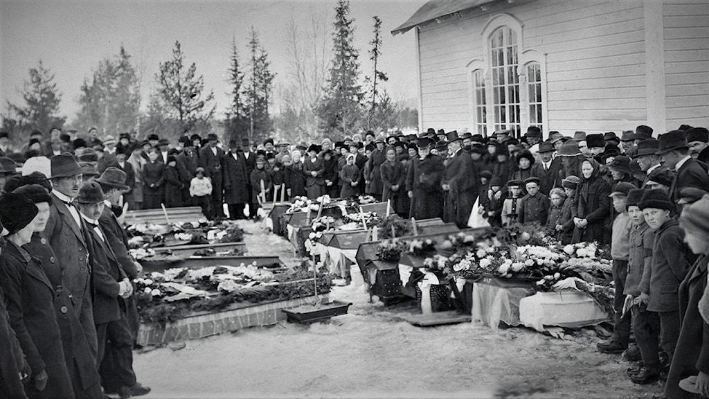 Svartvit bild med en stor folksamling klädda i svart utanför en kyrkbyggnad. På marken mellan människorna står en mängd begravningskistor.