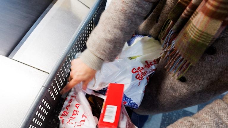 Ett par händer som packar ner mat i en plastkasse.