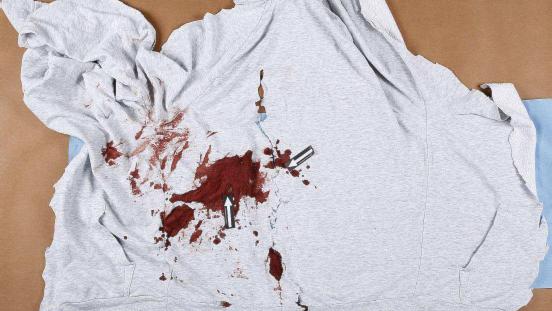 Grå tröja med blod på som föraren hade på sig när han blev skottskadad.