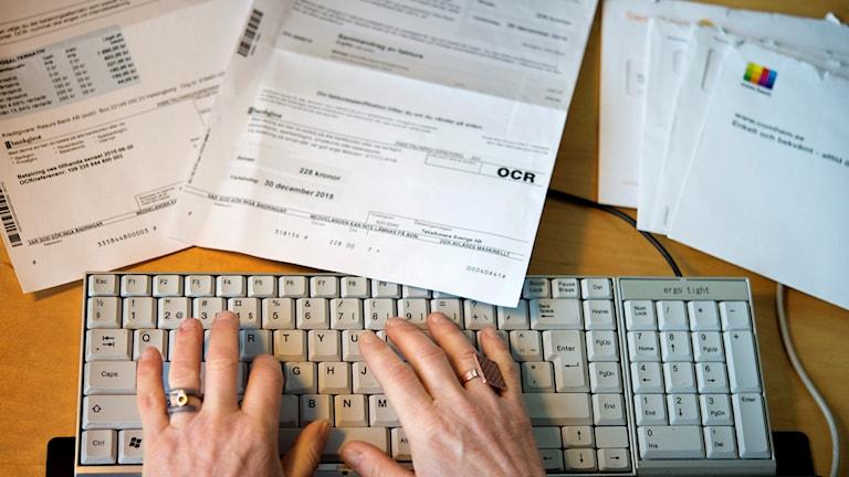 En bild på ett tangentbord och en mängd fakturor.