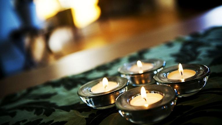 Fyra värmeljus på ett bord på en grön duk.