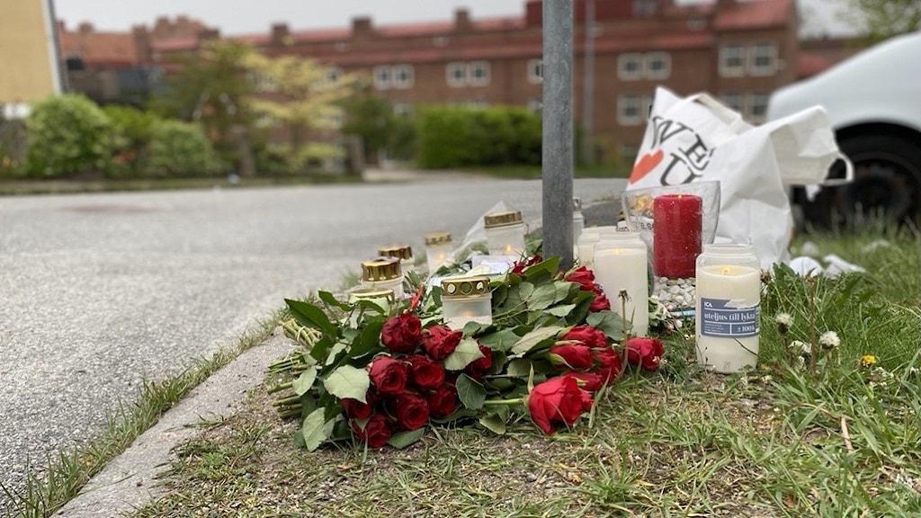 Blommor och gravljus på mordplatsen i Ronneby.
