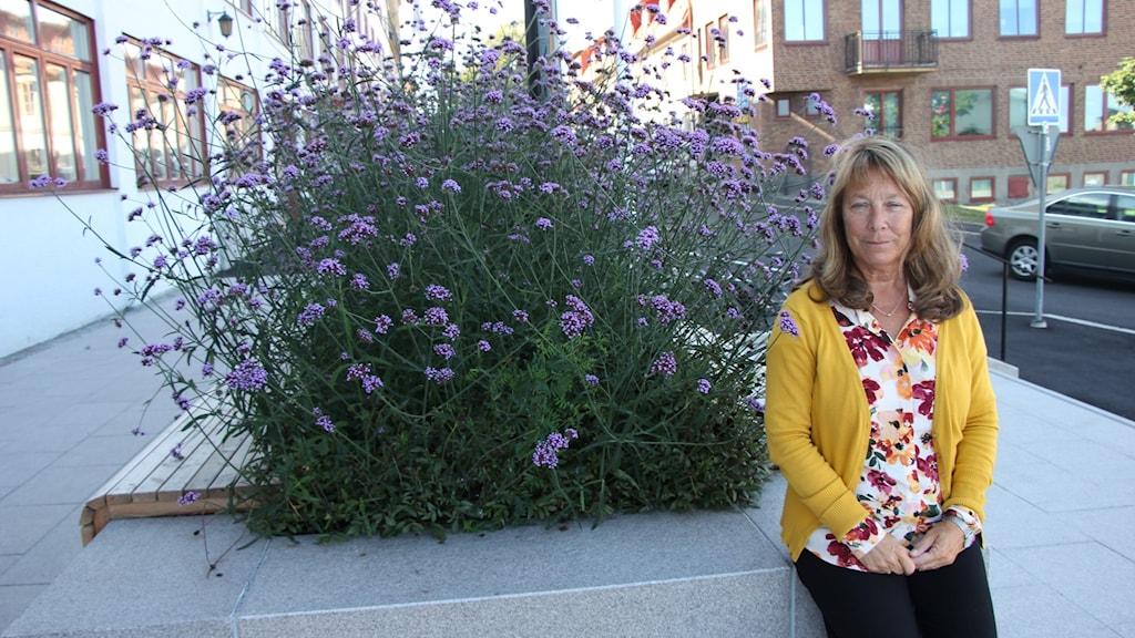 En kvinna står lutad mot en kant utanför kommunhuset i Karlskrona.