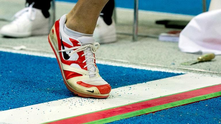 En gymnastikskobeklädd fot som får fullträff på plankan i tresteg.