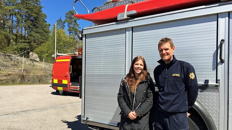 Caroline Sjöquist och Magnus Kärvhag står framför en brandbil.