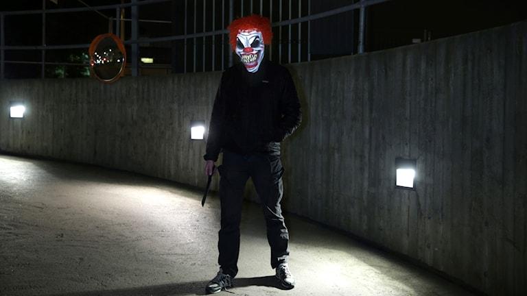En clown står i mörkret och håller i en kniv.