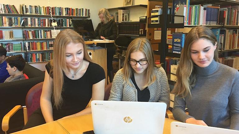Tre tjejer vid en dator i ett bibliotek.