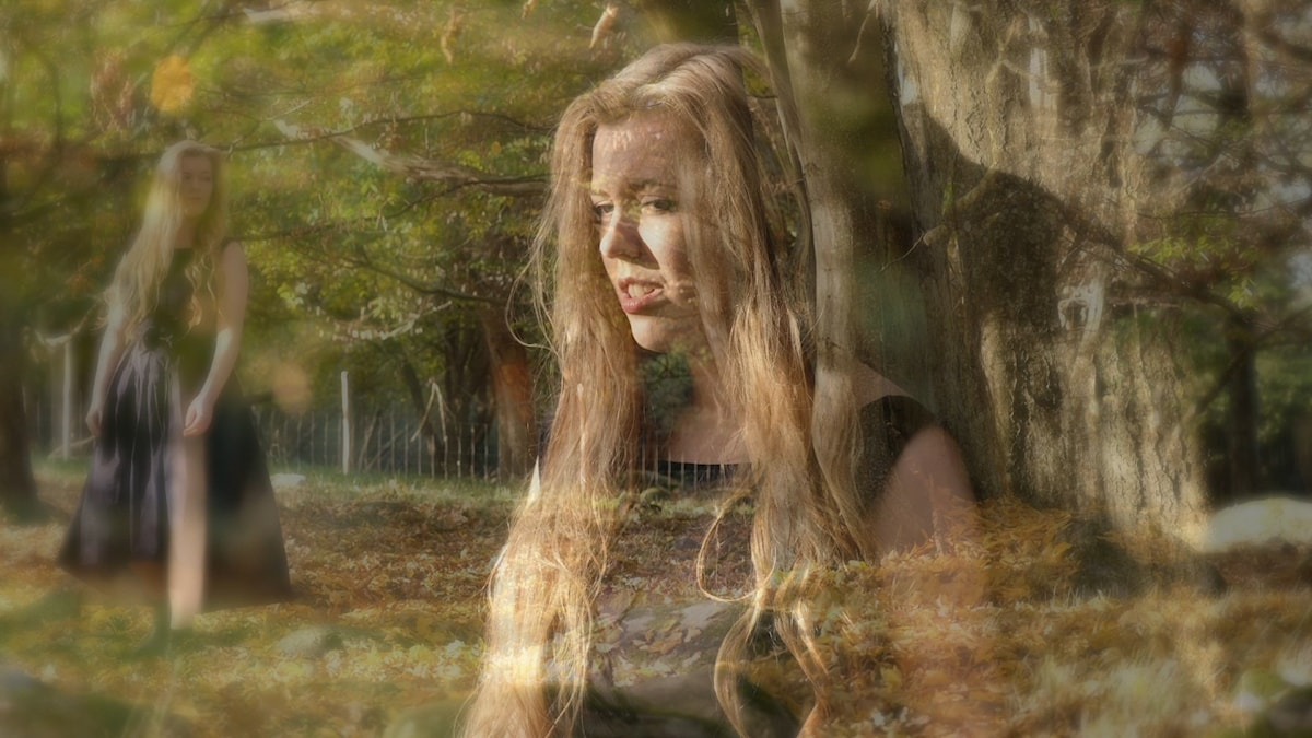 Erika Hansson står mot ett träd