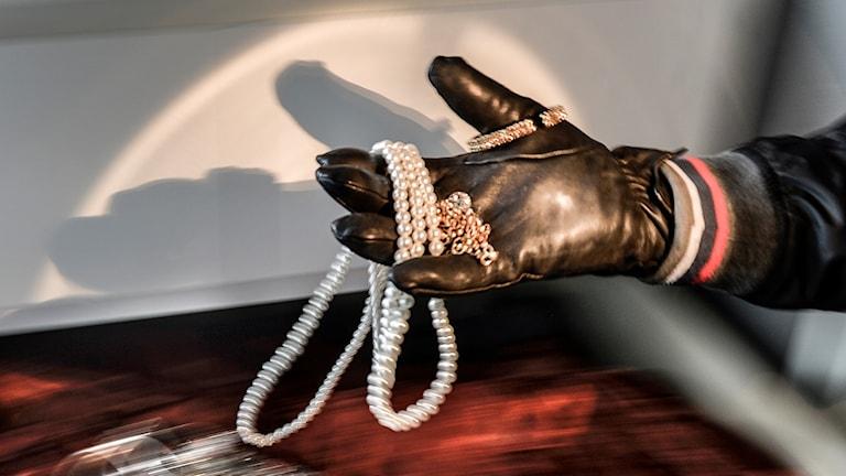 En handskbeklädd hand håller i flera smycken.