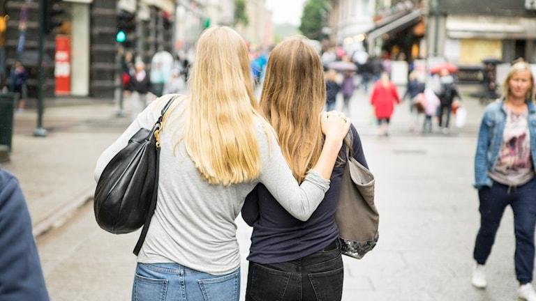 Två tjejer med långt hår sett bakifrån.