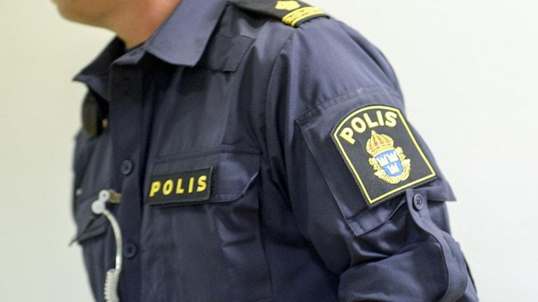 Polisens emblem på ärmen och bröstet på överkroppen på en polis.
