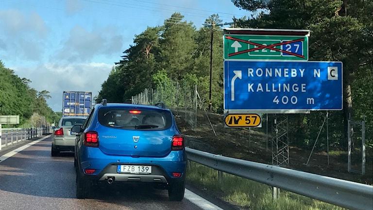 En blå bild framför en skylt där E22 är  överkryssad.